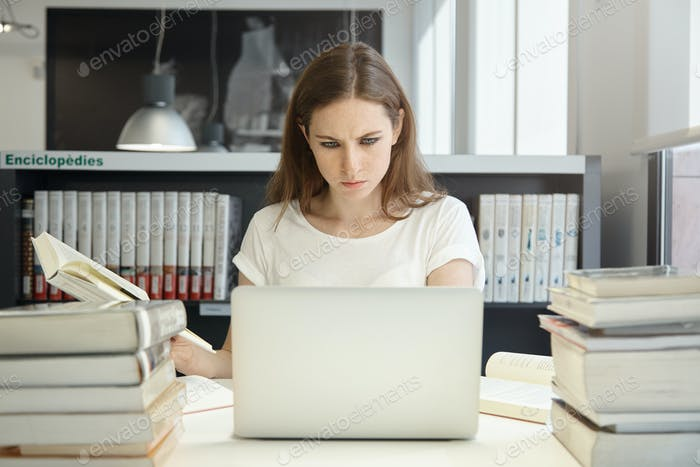 Portrait of female student sitting at the bookshelf and using laptop in the library, reading books,