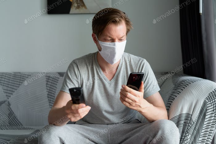 Young man with mask using phone while watching tv at home under quarantine