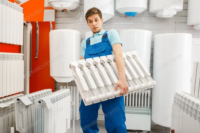 Plumber holds water heating radiator, plumbering