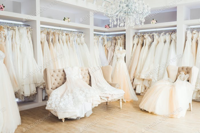 Beautiful wedding dresses on hangers in wedding atelier