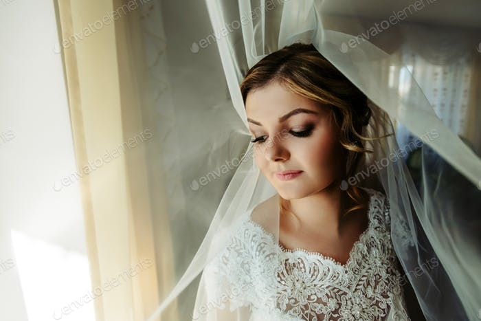 happy gorgeous blonde bride getting dressed in the morning, smiling under veil