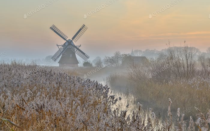 Wooden windmill in hazy landscape