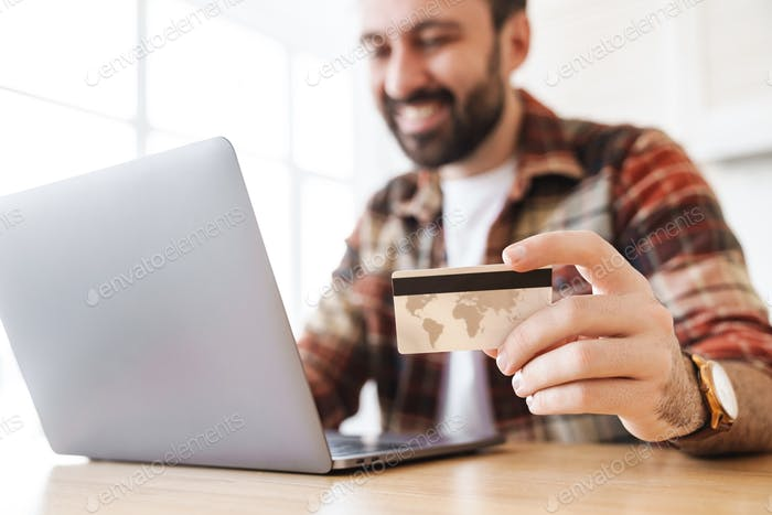 Portrait of cheerful man working with laptop and holding credit card