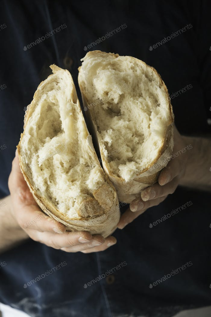 Close up of a baker holding a fresh baked white bread loaf torn in half.