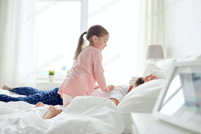 little girl waking her sleeping father up in bed