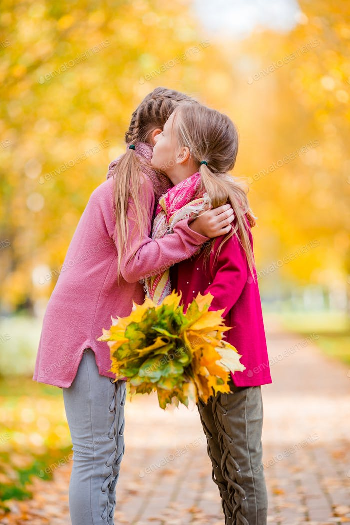 Little adorable girls at warm day in autumn park outdoors