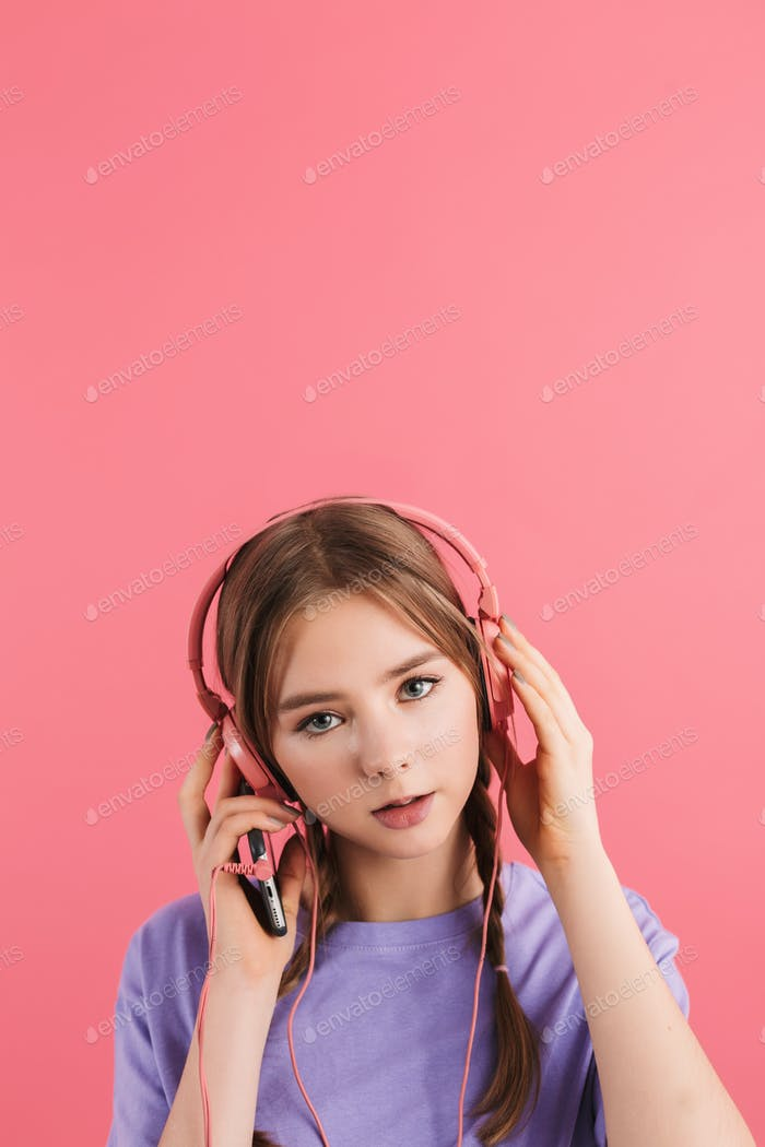 Young cute dreamy girl in lilac t shirt listening music in headphones thoughtfully looking in camera