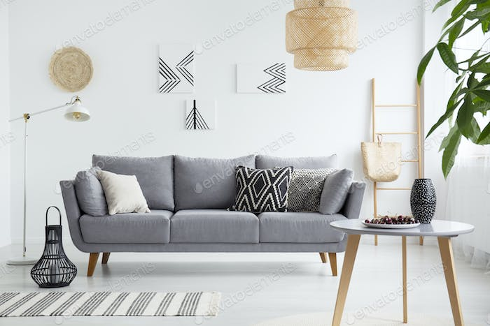 Real photo of a scandi living room interior with cushions on gra