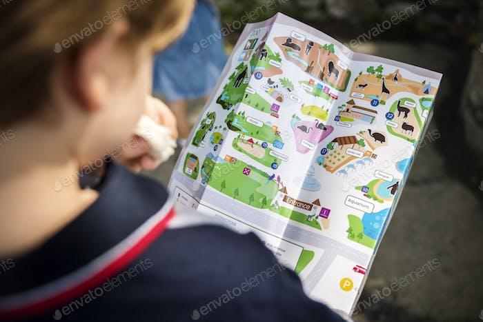 Rückansicht des jungen kaukasischen Jungen Blick auf den Zoo Karte