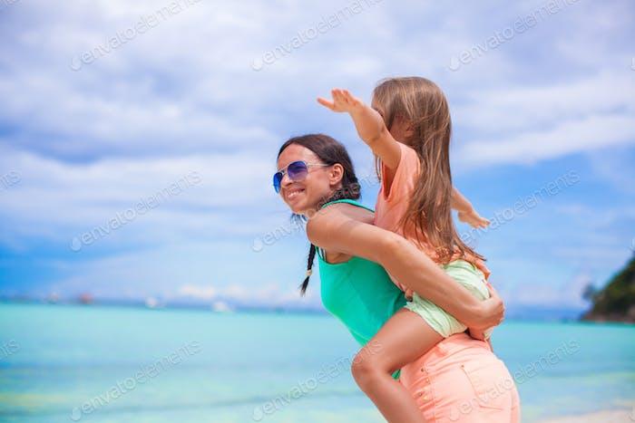 junge schöne Mutter und Ihr entzückend kleine Tochter flyinf wie ein Vogel bei tropischen Strand