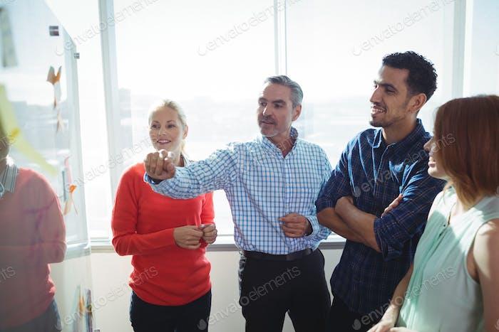 Business entrepreneurs discussing over whiteboard