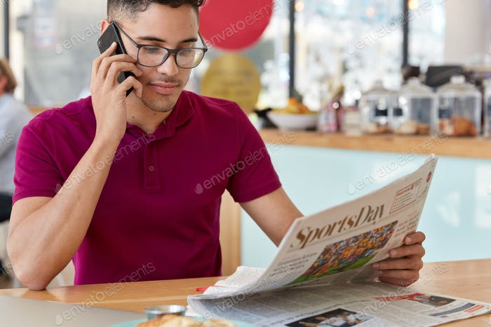 People and daily press concept. Cropped image of attractive male discusses latest news read in newsp
