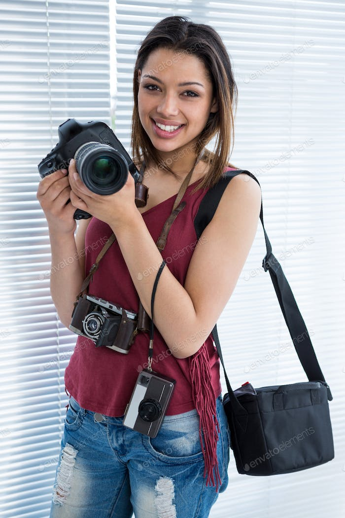Happy female photographer standing in studio