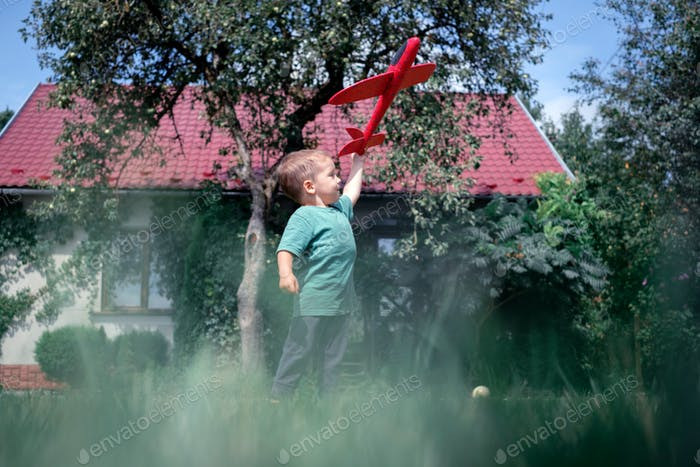 Happy kid playing with red airplane
