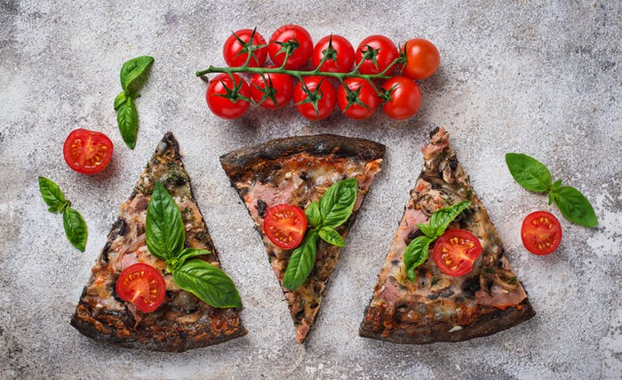 Pieces of  black pizza with tomatoes and basil