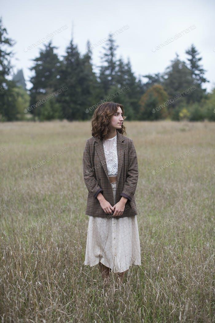 17-летняя девочка в твидовом блейзере, стоя в поле