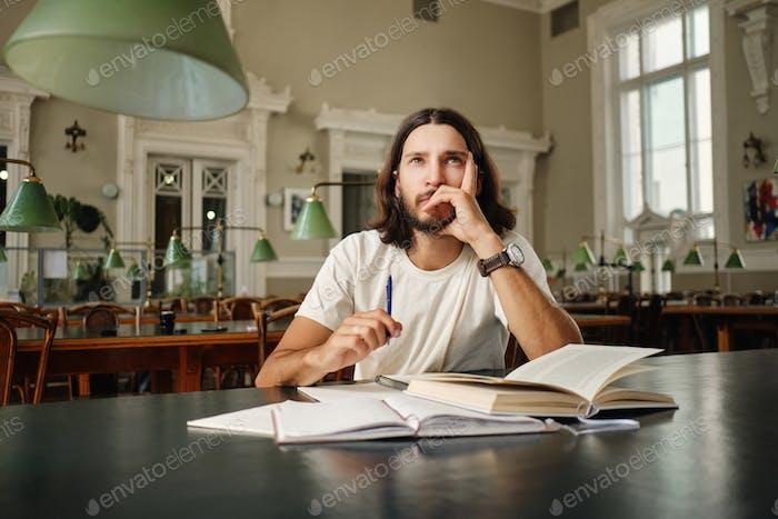 Wistful Student Typ, der sich auf die Prüfung vorbereitet und nachdenklich mit Büchern in der Bibliothek der Universität studiert