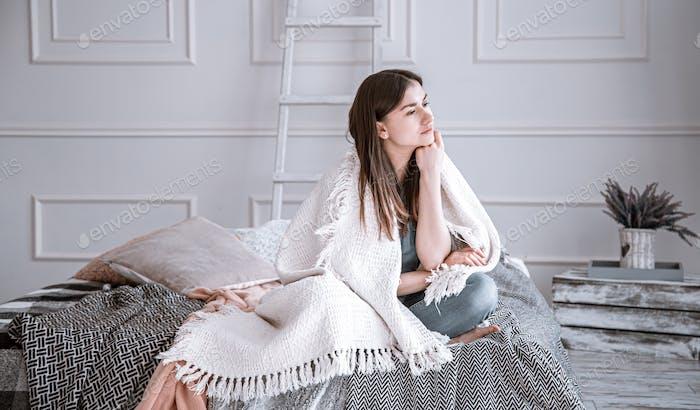 Eine junge, nachdenkliche Frau sitzt auf dem Bett.