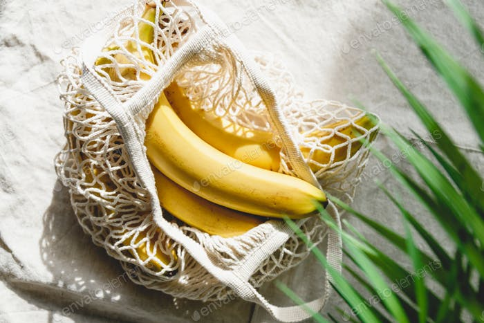 Bananas in a net produce bag on a linen napkin decorated with palm leaf