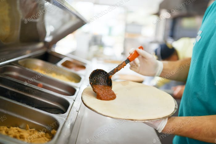 Chef puts tomato sauce on pizza workpiece. Close-up.