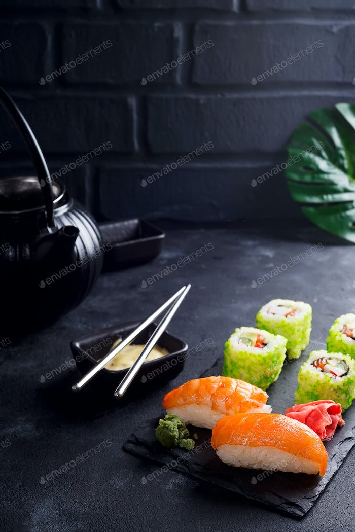 Sushi and rolls set served on black slate with metal chopsticks, black ceramic tea pot on a dark