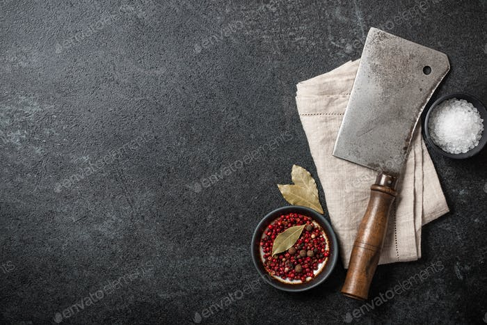 Cooking background with vintage butcher cleaver and spices on blackboard