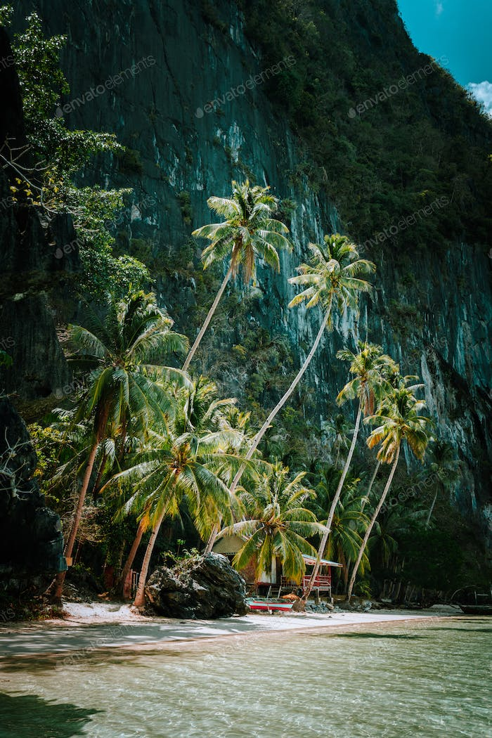 Tropical paradise beach surrounded by huge majestic mountains rocks, Philippines, Southeast Asia