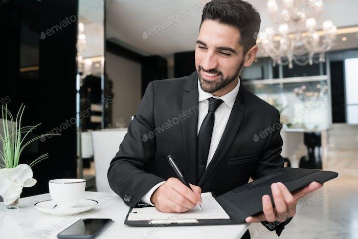 Businessman working at hotel lobby.