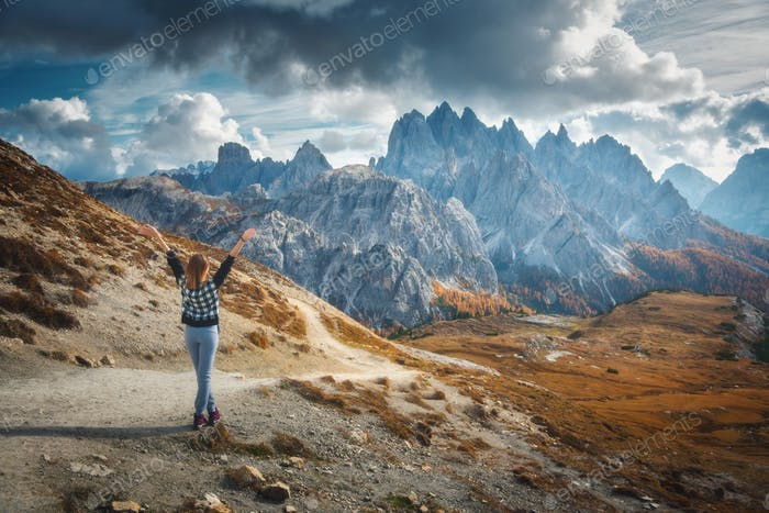 Woman with raised up arms and majestic mountains at sunset