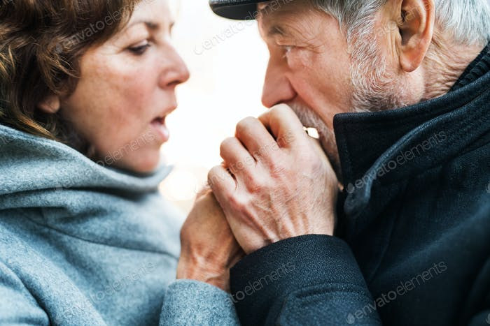 A close-up of senior couple standing outdoors, warming up hands when cold.