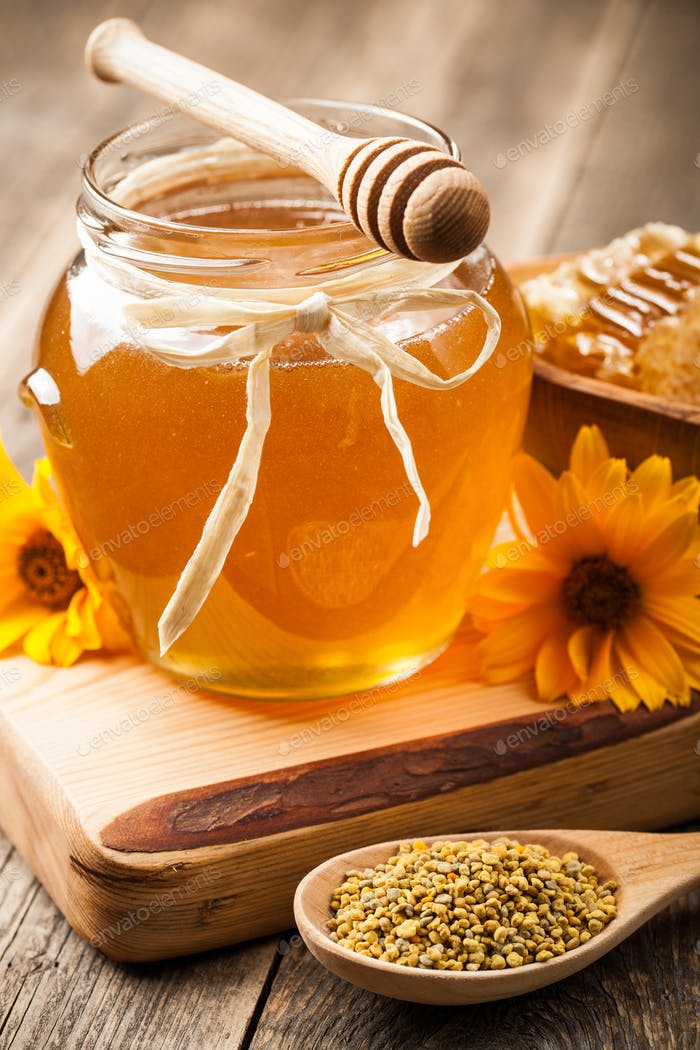 Honey in glass jar on wooden table