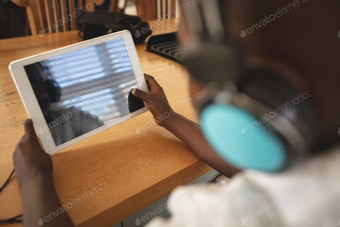 Rear view of african American boy using digital tablet at dining table in kitchen at home