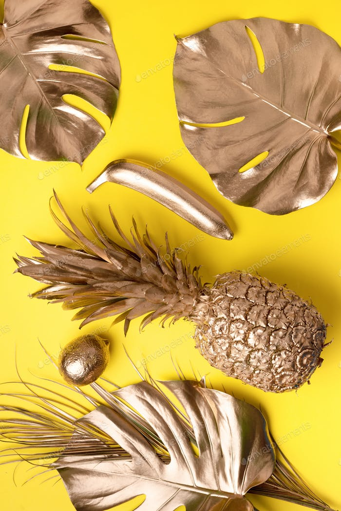 Creative layout. Gold pineapple and golden palm, monstera on yellow background with copy space. Top