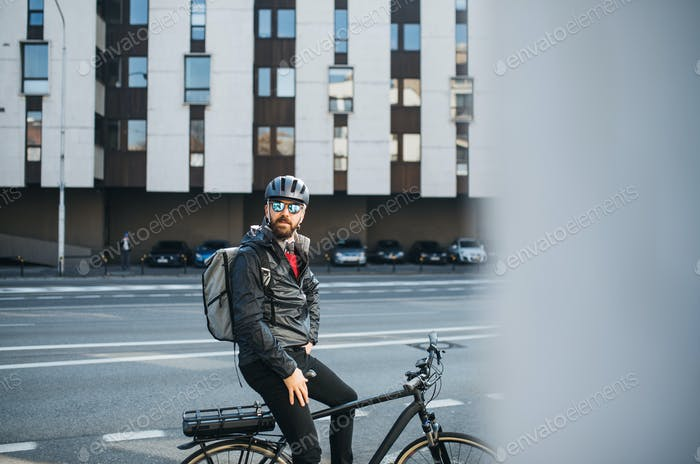 Male bicycle courier with backpack and sunglasses delivering packages in city.