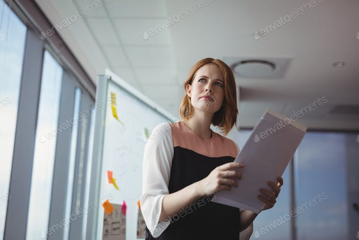Thoughtful executive holding documents