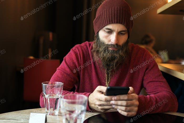 Bearded hipster typing on phone