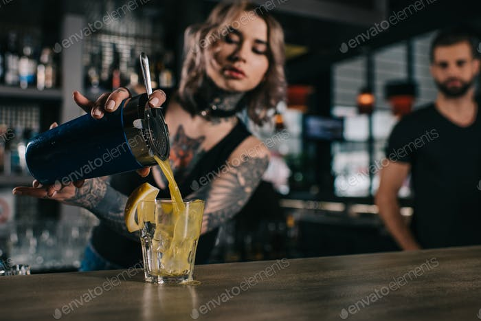 татуированный бармен готовит напиток в баре