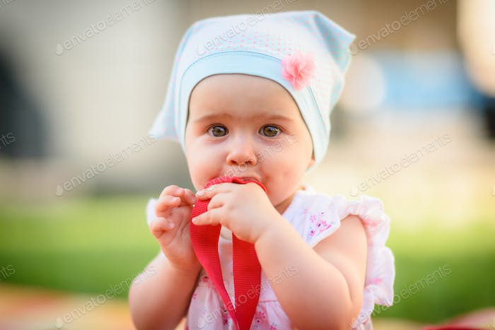 9 months old infant baby girl sits alone in garden grass on colorful blanket. Looking at camera and