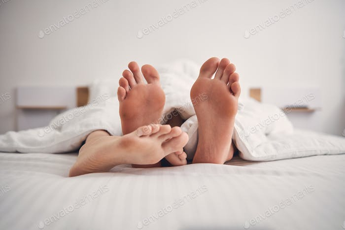 Close up of two people feet in bed