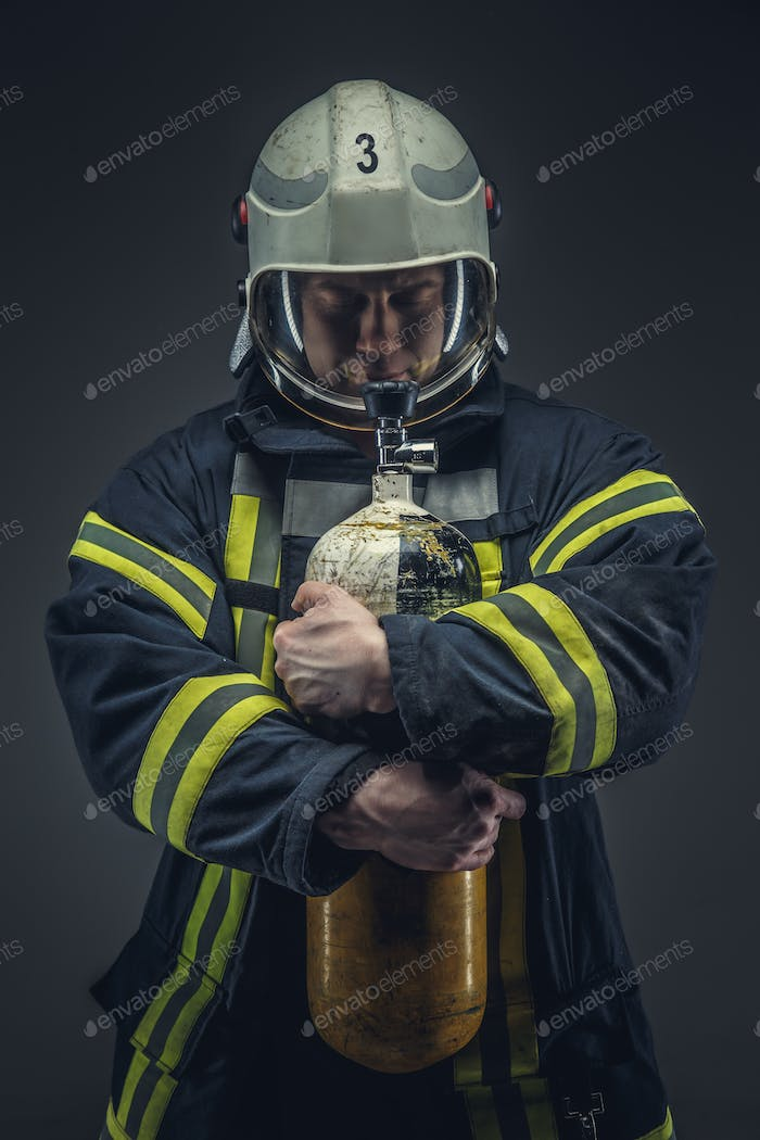 Firefighter rescue holds yellow oxygen tank.
