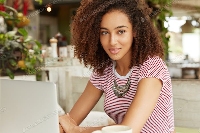 People, technology and lifestyle concept. African American clever female student works on diploma pa
