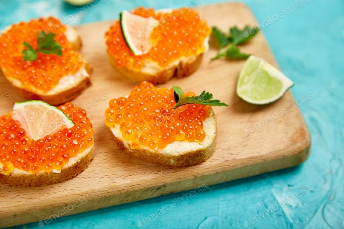 Salmon red caviar in bowl and Sandwiches with on wooden cutting board