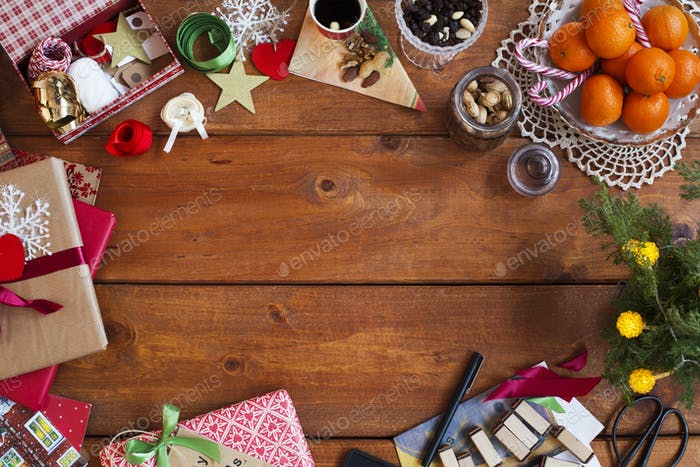 Directly above shot of Christmas gifts with decorations and food on wooden table