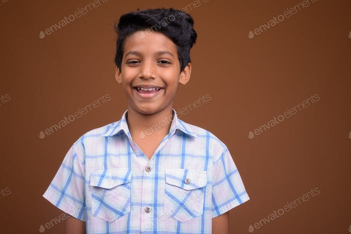 Young Indian boy wearing checkered shirt against brown backgroun