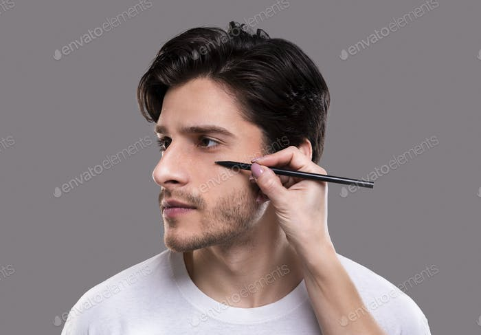 Plastic surgeon drawing guide marks on male patient face