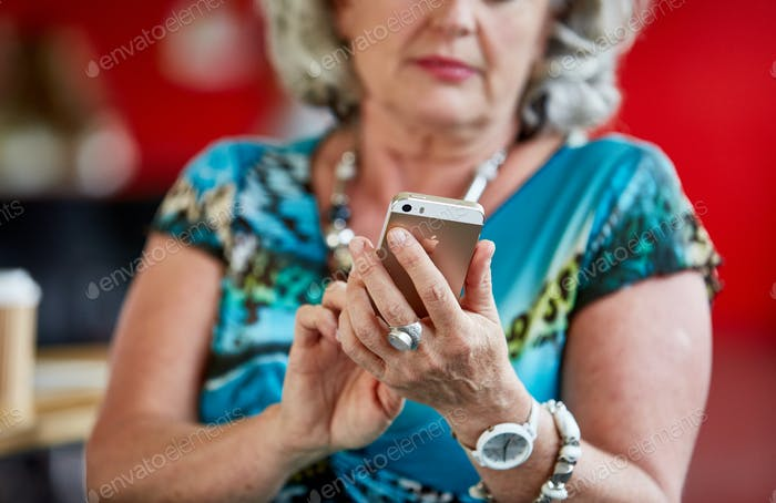 Confident female designer texting on a mobile phone in red creat