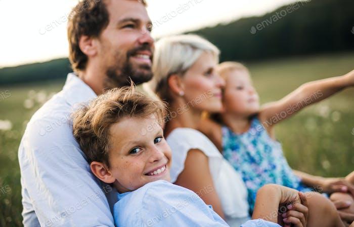 Junge Familie mit kleinen Kindern im Sommer Natur bei Sonnenuntergang.