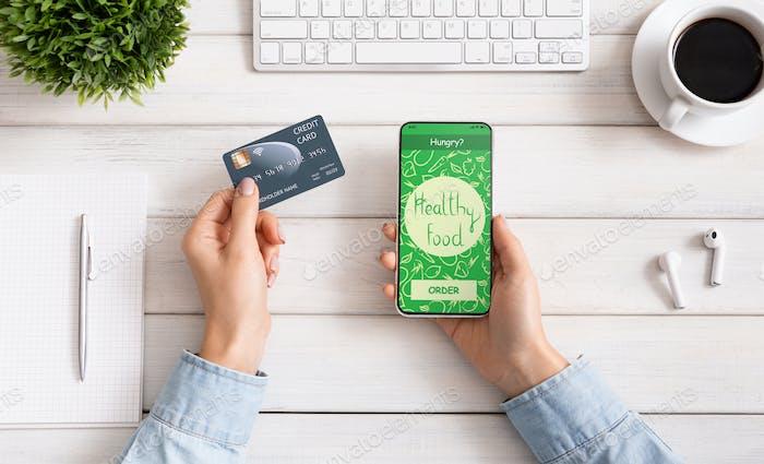 Weibliche Hand halten Telefon mit app Lieferung Lebensmittel auf dem Bildschirm