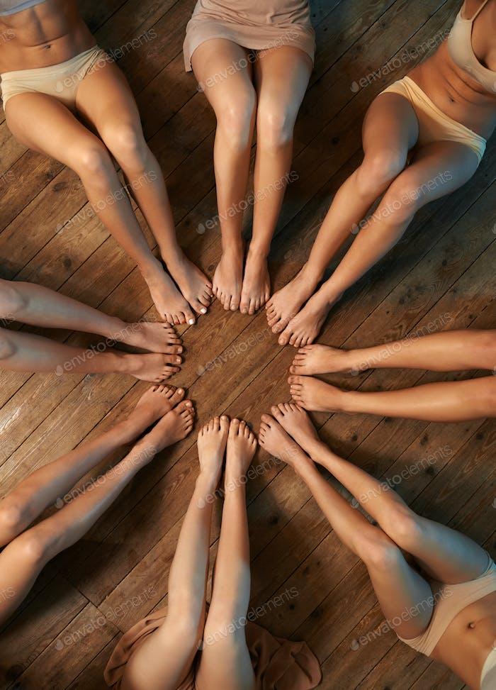 feet of dancers seated circle on  floor