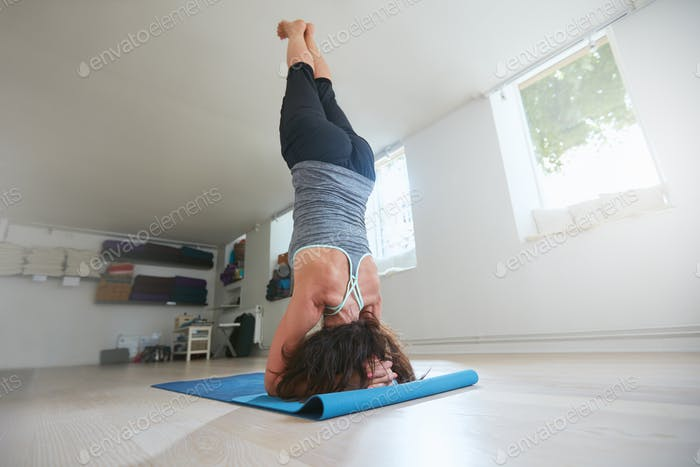 Fitness female practicing Salamba Sirsasana pose